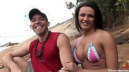 Hot transsexual babe and a guy have sex at a beach